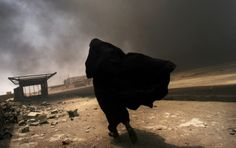 An Iraqi woman walks through a plume of smoke rising from a massive fire at a liquid gas factory as she searches for her husband in the vicinity in Basra, Iraq, May Lynsey Addario. War Photography, Street Photography, Documentary Photography, Amazing Photography, Iraqi Women, Fotojournalismus, Human Rights Issues, Bagdad, World Press
