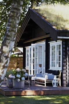 .I love the white doors and windows used with the darker wood cabin. Provides a great contrast, Wonderful baskets. This is so charming and so peaceful. Notice the grass roof as well.