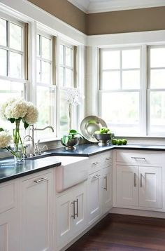 White kitchen cabinets, farm sink, and dark countertop. Love how the windows take the place of the wall cabinets, it brings tons of light into the room.