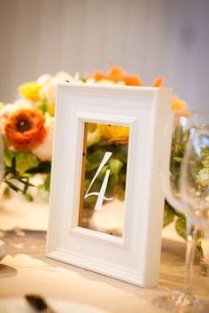 Marcos super originales con vidrio como números para mesas de boda.