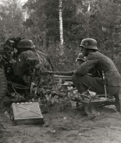 "German soldiers in action in a forest with a 37mm Pak 35/36 during Operation Barbarossa, 1941. The soldier from left is wearing early pattern camouflage smocks and helmet cover in a ""Plane Tree"" pattern."