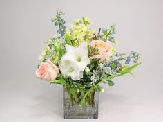 glad to meet you: white gladiolus with soft peach Alejandro roses, creamy stockflower, light blue delphinium and dusty miller.