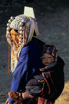 Thailand | An Akha woman, wearing a traditional beaded headdress, travels with her child on her back | © Christophe Boisvieux/Corbis