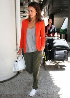 Jessica Alba, on-the-go at an airport, rocks olive cargo pants, a crew neck tee, and an orange blazer with white slip-on sneaks and a white bag. Jessica Alba Outfit, Jessica Alba Style, Pantalon Orange, Mode Outfits, Casual Outfits, White Slip On Sneakers, Olive Pants, Green Cargo Pants, Look Blazer
