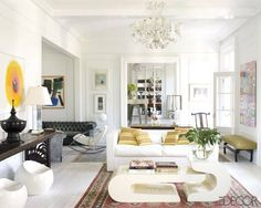 A white, eclectic living room punctuated by modern white furniture incur the organic shapes