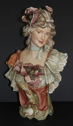 Royal Dux ~ Bohemian Porcelain ~ Bust of a Woman ~ She has mauve flowers in her hair and bodice ~ She has a rust ~ to beige ~ to green Dress trimmed in beige lacey sleeves ~ She hasa blue silk ribbon around her neck in a bow