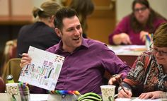 Roger Swartzendruber of Arlington Heights shows his work to those seated at his table during the Coloring for Grown-ups program at the Arlington Heights Memorial Library.