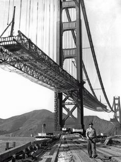 """A workman walks on the levee that connects Fort Point to the south tower of Golden Gate Bridge. Below the bridge, the enormous safety net can be seen: it saved the lives of 19 men who formed the """"Halfway to Hell Club"""" (c 1936)"""