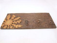 Perchero con eguzkilore tallado en madera de roble en altorrelieve, tratado con betún judaico a dos tonos con tres perchas de hierro artesanales.  Dimensiones:60×25cm.aprox.