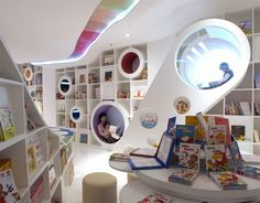 Amazing playground inspired children's bookstore, designed by SAKO architects, is located in Beijing, China.      The walls of are covered with bookshelves and round windows double as relaxing reading areas.