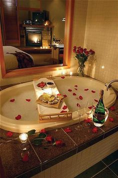 Romantic bath with candles and rose petals.