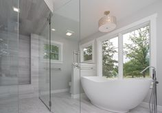 Owners Suite: ceramic tile floor, free standing tub, coordinating tile shower surround, zero clearance shower with glass walls, large windows, lots of natural