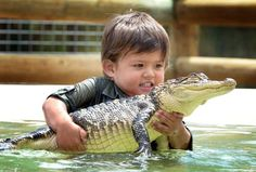 3yr old Charlie Parker plays with a North American baby alligator named Gump
