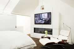 White bedroom with reclining Eames lounge chair, modern fireplace, and mounted TV