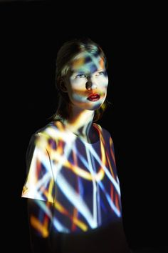 Young Woman covered in multicolored lights / Gem Fletcher