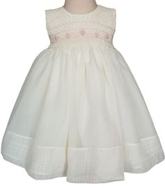 Our new 'Ivory organza dress with light pink roses' is absolutely precious! It is the perfect dress for your little lady on any and every special day! Fully lined, this dress is flowing and beautiful! There is a panel of hand smocking on the chest of the sleeveless dress. On the ivory colored floss is a hand smocked design of light pink roses. With a long organza sash in the back.