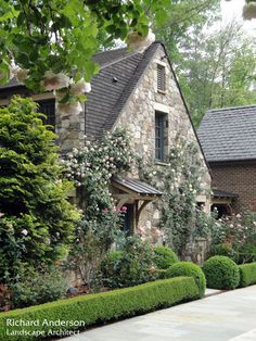 Stone cottage style home near Atlanta, Georgia. Landscape architect Richard Anderson included a profusion of climbing roses clinging to the stone facade and cascading over the covered entry way.