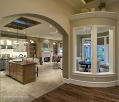 Love the shelves around the fireplace, and the island with seating  and a skylight above, and the curved breakfast nook with windows facing inside.
