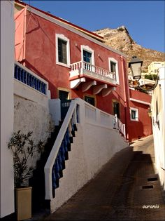 A view from a neighborhood of Christos. Above de red house there's a glimpse of de northern tip of de Castle, in Leros, Dodekanisos, South Aegean_ Greece