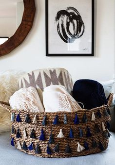 Erica's finished DIY tassel-edge basket serves as the perfect place to store extra throw blankets so they're within arms reach for family movie nights cuddling up on the new white linen couch! See more from our Honestly WTF Home Tour and Modern Living Room Makeover with The Studio at One Kings Lane: Inside Blogger Erica Chan Coffman's Oakland, CA Pad over on our Style Guide!