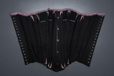 Black Cotton Corset With Spoon Busk, Pink Flossing Embroidery & Woven Trim, c. The Underpinnings Museum. Photography by Tigz Rice. Museum Collection, Black Cotton, Underwear, Museum Photography, Embroidery, Pink, Spoon, Britain, Tops