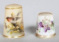 Royal Worcester porcelain thimbles (2). The blush ivory ground painted with a robin amid flowers over a gilt rim, 2.6 cm., and another painted with scattered flowers, (cracked and s.d.), 1.9 cm. Update: Sold for £20 (about US$39.61) plus Premium and tax.