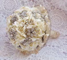 Este ramo de novia cuenta con elegantes camelias en color blanco roto, Broches de strass .Se termina con un mango de raso envolviéndolo en una fina...