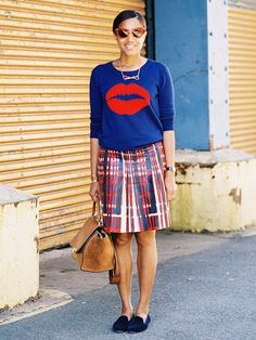A graphic sweater is paired with a plaid skirt, smoking slippers, and feminine accessories