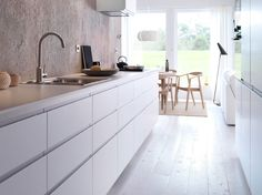 A white kitchen with aligned doors, a white floor and a grey concrete wall