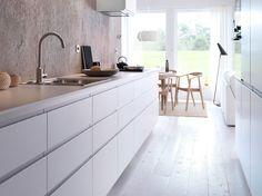 Biała kuchnia z równymi drzwiami, białą podłogą i szarą, betonową ścianą