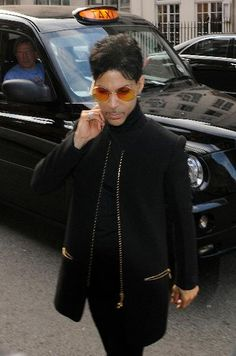 Prince spotted walking in Central London, England. July 4th, 2011 half length black trousers jacket sunglasses shades taxi cab car.