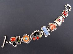 jewelry image of Sterling Silver, Jasper with Onyx and Tourmaline, Topaz on Chinese Carnelian, Onyx with Carnelian and Peridot, Blue Coral, Citrus Chalcedony, Garnet on Montana Moss Agate with Carnelian, Iolite on Carnelian. $1100.