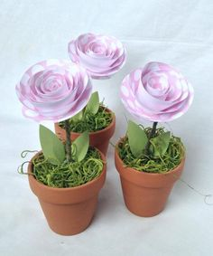 This is a set of three mini terra cotta plant pots. Each is filled with a 2.5 inch paper rose on a wrapped wire stem and has two leaves to finish to look. The pots stand 2.5 inches tall, and the total