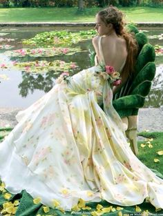 Girl sitting in green velvet chair  in wearing  an ivory gown with yellow roses