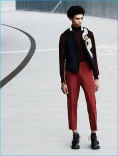 Standing tall, Sol Goss wears a Dries Van Noten vest, Oscar Jacobson sweater, CMMN SWDN trousers, and Dior Homme shoes.