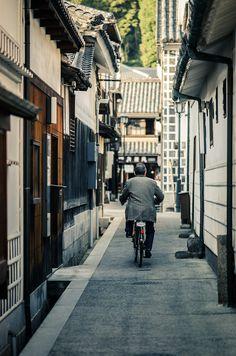 A man rides his bike through an alley at the Kurashiki Bikan historical district in Okayama Prefecture, Japan
