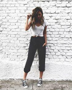 8 dicas para você incrementar o visual do dia a dia. T-shirt branca com nozinho na cintura, calça de moletom preta com barra levantada, tênis all star preto