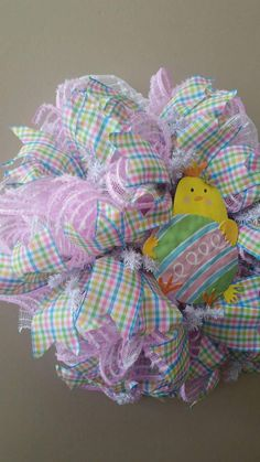 Simple and cute handmade Easter Wreath that perfect to leave up all Spring long. Pastel ribbons, pink and white mesh all surround a cute yellow chick holding an egg. Could it be any cuter? 21 x 21 x 8 finished size **Please note, the mesh has been cut so there will be some