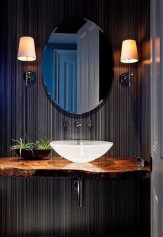 petite salle de toilette sombre et élégante avec un miroir ovoïde, un plan vasque bois brut et une vasque à poser en verre blanc