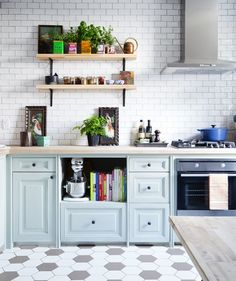 Parisian inspired. Light blue cabinets. Classic white subway tile. Black (or grey?) and white hexagon tiled floor.
