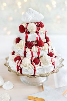 Meringue Christmas tree with whipped coconut cream, raspberries and white chocolate truffles drizzled with mulled berry coulis
