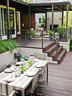 The two-tiered design welcomes backyard views and casual gatherings. A teak top dining table with a metal base stays true to the deck's clean, modern design, while seasonal greens and contemporary pottery create an inviting tablescape.