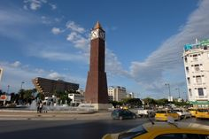 pubic square - monument - clock - water jet - lamppost - street light - people - sky - clouds - cars - taxis - building - road - traffic - Avenue Bourguiba - Tunis - DUBON Photographie