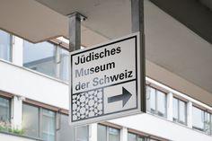 (De) Jüdisches Museum der SchweizGestaltung des Eingangsbereiches des Jüdischen Museums der Schweiz in Basel. Das Konzept der Signaletik vereint das David-Muster des Judentums und den Pfeil zwecks Wegleitung und lädt in elegantem Dunkelblau und ohne Sch…