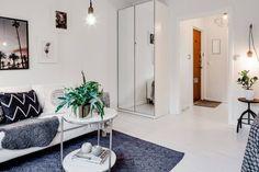 W salonie ustawiono niezbyt szeroką, ale za to wysoką szafę o lustrzanych frontach. Biały kolor nawiązuje do bazowej barwy aranżacji. Lustra odbijają salon, delikatnie optycznie powiększając przestrzeń.