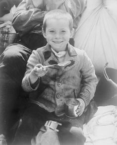 A Polish boy liberated by Americans at a concentration camp enjoys his first meal of US Army rations.