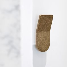 Close up of the Bellagio joinery handle finished in a tumbled brass treatment. Mounted vertically on a cupboard joinery door.
