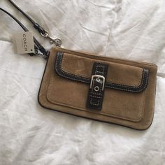 NWT Coach Wristlet Suede and brown lining Coach new with tags Wristlet. A few marks one on the front and one on the back. Shown in the last two pictures. Still in very good condition never used. 8 inches long 4.5 inches tall Coach Bags Clutches & Wristlets