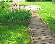 wood plank walking path, I'd like something like this in my garden but curved, rather than just straight. Saves things like stones getting everywhere from a gravel path, but easier to mow than stepping stones