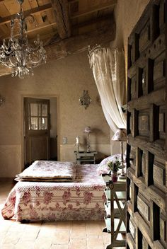 Summer in Provence; I love the aged wood a and crystal chandelier. Beautiful bedding and drapes.